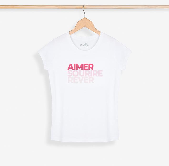 T-shirt femme rose posé sur un cintre et son portant