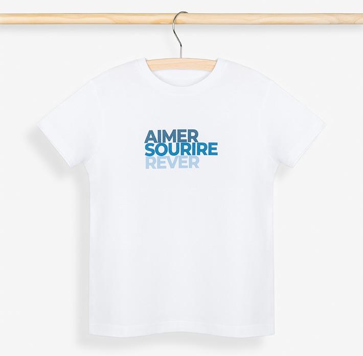 T-shirt garçon bleu posé sur un cintre et son portant