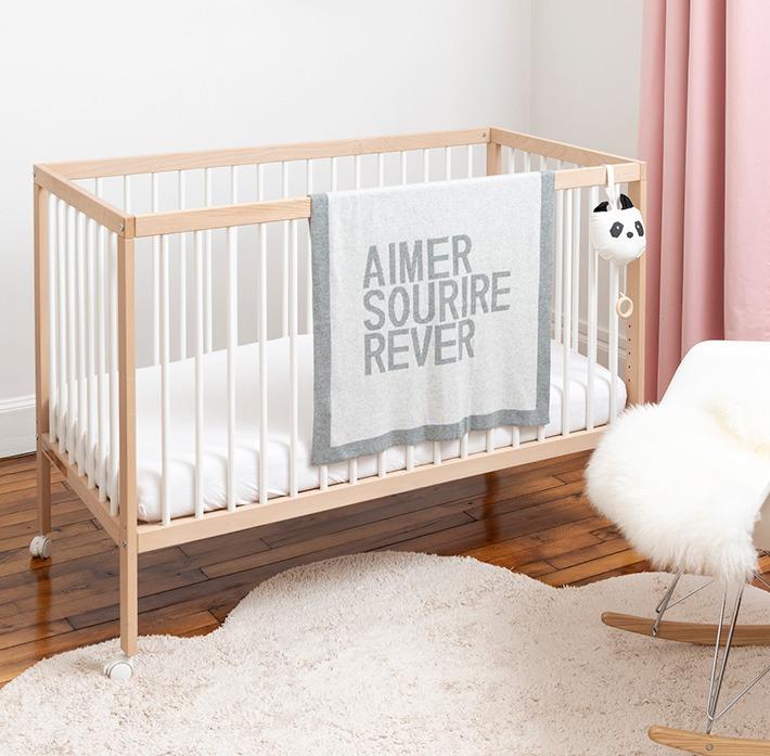 Plaid gris clair posée sur un lit bébé
