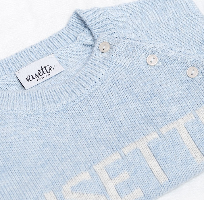 Zoom maille pull bébé bleu avec logo et étiquette