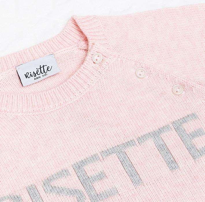 Zoom maille pull bébé rose avec logo et étiquette