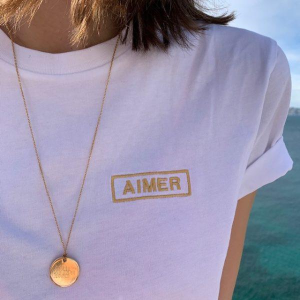 T-shirt AIMER brodé blanc gold porté mer zoom + médaille gravée