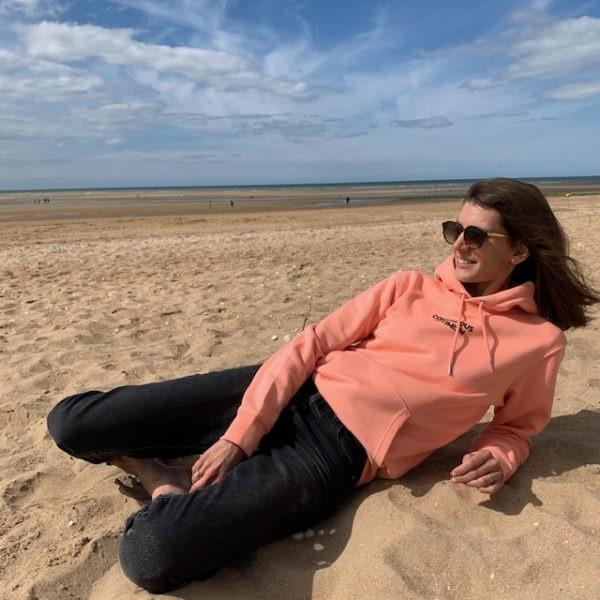 Sweat à capuche unisexe coloris sunset porté sur la plage